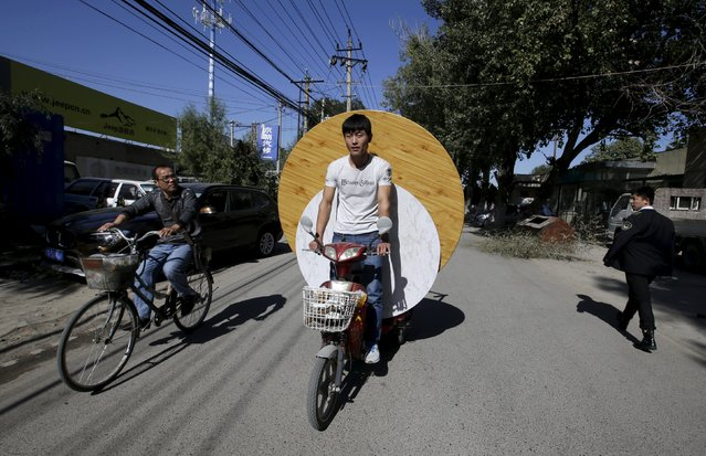 A man rides an electric bicycle carrying dining tables along a street inside a residential area for migrant workers on the outskirts of Beijing, China, October 13, 2015. (Photo by Jason Lee/Reuters)