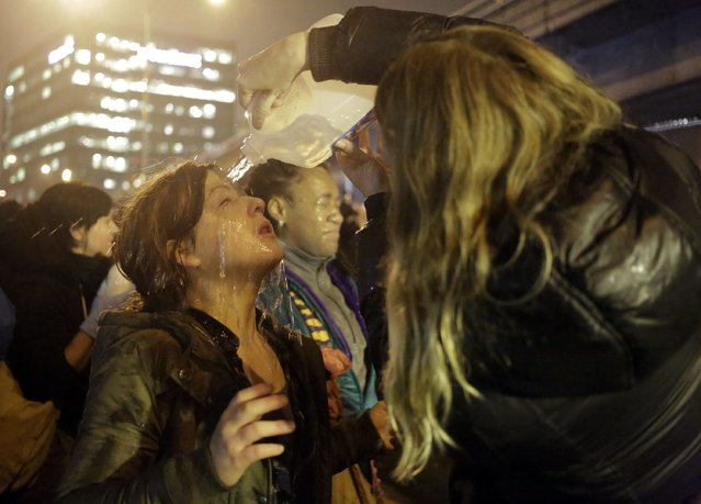 A woman gets water poured on her face after police pepper sprayed demonstrators attempting to stop traffic on Interstate 5 following the grand jury decision in the Ferguson, Missouri shooting of Michael Brown, in Seattle, Washington November 24, 2014. (Photo by Jason Redmond/Reuters)