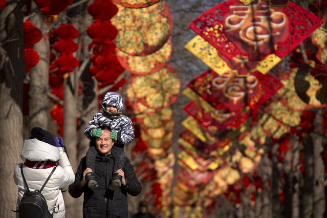 In this Saturday, February 10, 2018, file photo, a man holds a child as they pose for a photo near a pathway decorated for the Lunar New Year at a public park in Beijing. (Photo by Mark Schiefelbein/AP Photo)