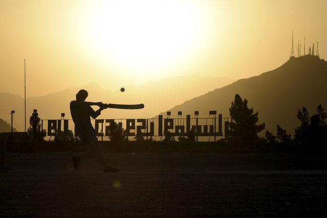 Youths play cricket at sunset at the Nader Khan hilltop in Kabul on September 22, 2020. (Photo by Wakil Kohsar/AFP Photo)