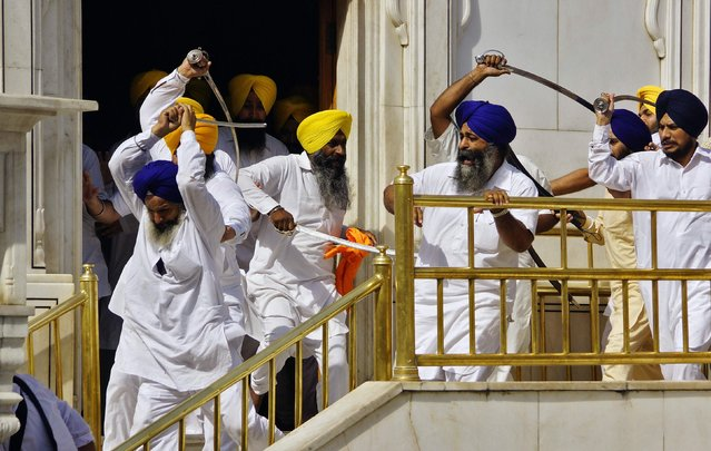 Sikhs wield swords as they clash inside the complex of the holy Sikh shrine, the Golden Temple, in the northern Indian city of Amritsar, in this June 6, 2014 file photo. (Photo by Munish Sharma/Reuters)