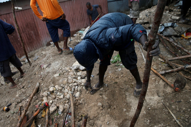 Men build a makeshift house at a camp for displaced people while Hurricane Matthew approaches Port-au-Prince, Haiti, October 3, 2016. (Photo by Carlos Garcia Rawlins/Reuters)