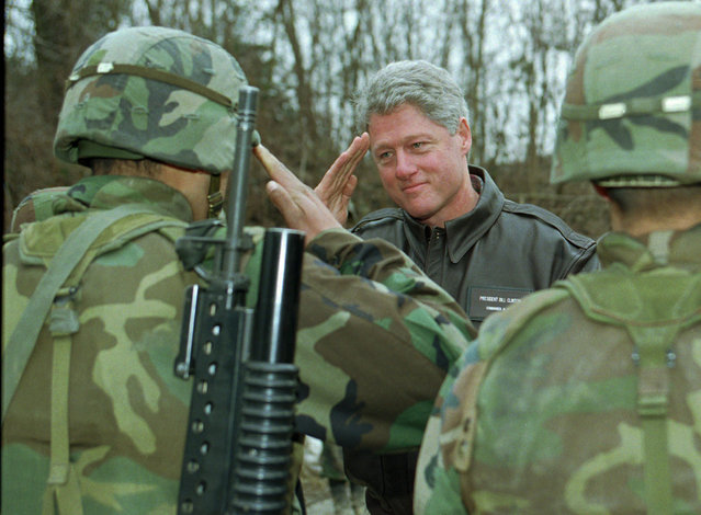 President Bill Clinton is saluted by a U.S. soldier while he reviewed the troops at tht Tuzla air base in northwestern Bosnia,  Saturday, January 13, 1996. President Clinton paid a front-line visit with U.S. forces in Bosnia, telling troops weary of mud and cold they re carrying out  a mission of heroes. (Photo by Greg Gibson/AP Photo)