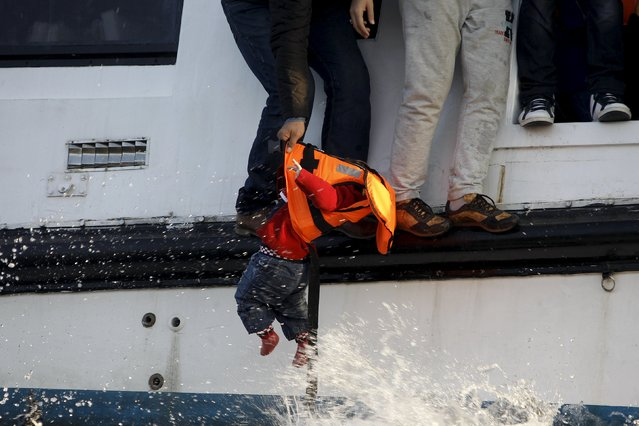 A refugee prepares to hand over a toddler to a volunteer lifeguard as a half-sunken catamaran carrying around 150 refugees, most of them Syrians, arrives after crossing part of the Aegean sea from Turkey on the Greek island of Lesbos, October 30, 2015. There were no casaulties amongst the refugees who were travelling on the catamaran, according to a Reuters witness. (Photo by Giorgos Moutafis/Reuters)