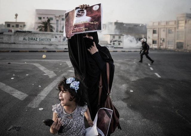 A Bahraini woman, standing with her daughter, holds up a picture of Abd Al-Ghani Al-Rayes during clashes following his funeral procession in the village of Diraz, west of Manama on April 1, 2013. Al-Rayes, who was 66-years old, died in front of a police station following what medics presume was a heart-attack, as he was trying to find out what happened to his arrested son, family said. (Photo by Mohammed Al-Shaikh/AFP Photo)