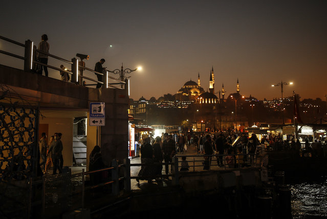 Backdropped by the Suleymaniye Mosque people stroll along the banks of the Bosporous in Istanbul, Turkey Friday, October 23, 2020. In much of Europe, city squares and streets, be they wide, elegant boulevards like in Paris or cobblestoned alleys in Rome, serve as animated evening extensions of drawing rooms and living rooms. As Coronavirus restrictions once again put limitations on how we live and socialize, AP photographers across Europe delivered a snapshot of how Friday evening, the gateway to the weekend, looks and feels. (Photo by Emrah Gurel/AP Photo)