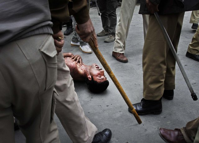 A Kashmiri government employee shouts as policemen beat him during a protest in Srinagar, India, on April 10, 2013. (Photo by Mukhtar Khan/Associated Press)