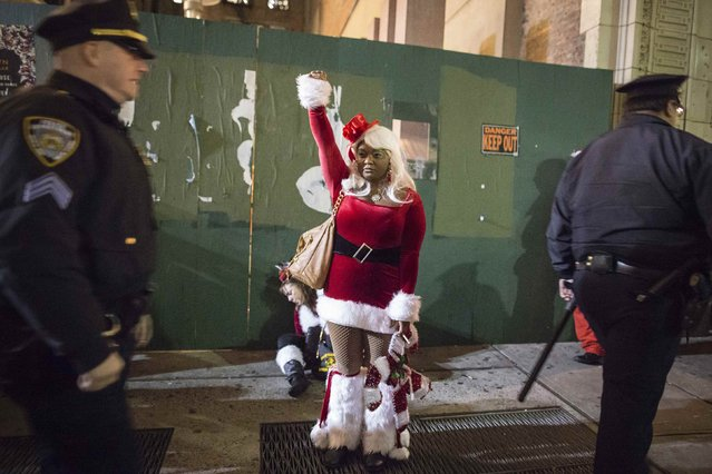 A woman gestures as she blocks a drunken reveler from police while taking part in SantaCon through Midtown Manhattan, New York  December 13, 2014. (Photo by Elizabeth Shafiroff/Reuters)