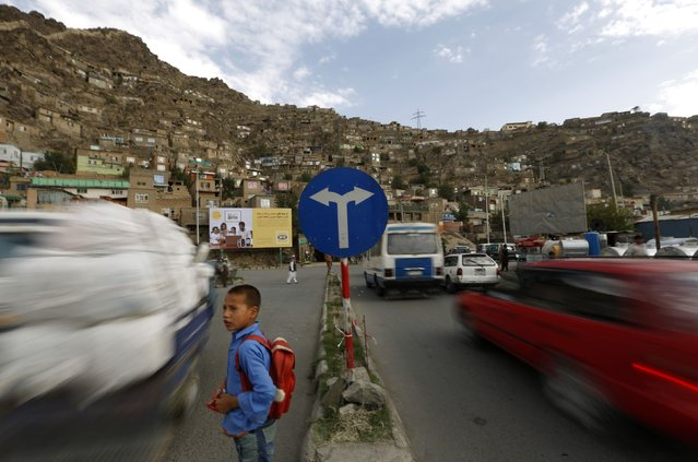 A schoolboy waits before crossing a street near a traffic sign in Kabul August 31, 2014. (Photo by Mohammad Ismail/Reuters)