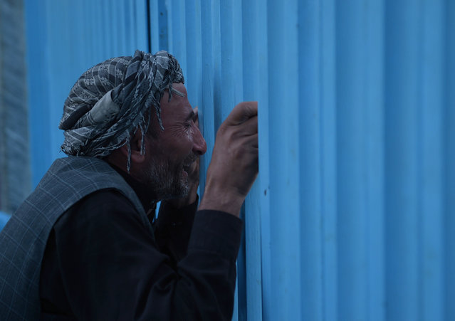 An Afghan man who lost his father in a gunmen attack weeps at the main gate of the Karte Sakhi shrine in Kabul on October 12, 2016. Gunmen targeted Shiite pilgrims in Kabul late on October 11, killing at least 14 people as they gathered to celebrate Ashura, one of the most important festivals on the Shiite calendar, officials said. (Photo by Shah Marai/AFP Photo)