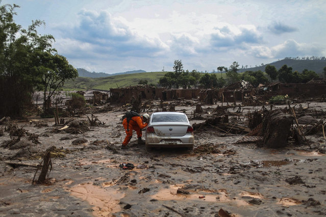 Firefighters search for victims in the mud after an industrial waste dump collapsed, in Bento Rodrigues in Mariana, Brazil, 08 November 2015. Retaining walls that burst open on 05 November at a mining complex set off an avalanche of mud and mineral residues that buried dozens of homes in the southeastern Brazilian city of Mariana and left at least one person dead, 16 injured, 13 missing and 530 homeless. (Photo by Antonio Lacerda/EPA)