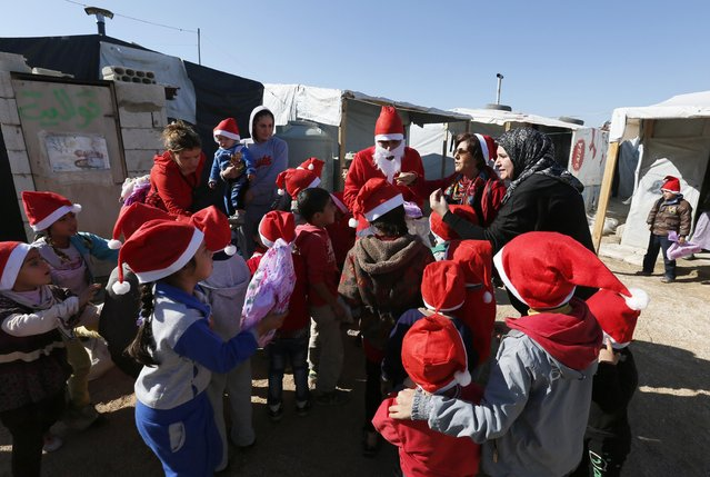 A man dressed as Santa Claus from SAWA, a non-governmental organisation, delivers toys to Syrian refugee children at a refugee camp in Bar-Elias in the Bekaa valley December 24, 2014. (Photo by Jamal Saidi/Reuters)