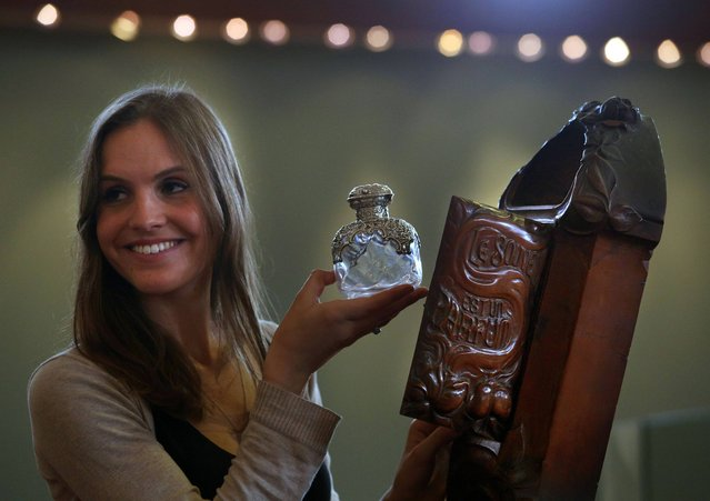 Lydia Stoker staff member at Lyon & Turnbull in Edinburgh, looks at a rare art nouveau carved perfume bottle stand valued at £8,000, designed by Henri Hamm to be auctioned on the 8th of May 2013. (Photo by  David Cheskin/PA Wire)