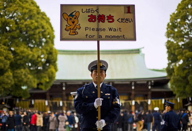 A police officer holds a sign asking visitors to wait as they line up to pray on the first day of the new year at the Shinto Meiji Shrine in Tokyo January 1, 2015. (Photo by Thomas Peter/Reuters)