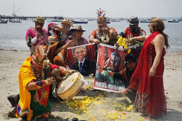 Shamans holding posters of U.S. President Barack Obama and Cuba's President Raul Castro, perform a ritual of predictions for the new year at Agua Dulce beach in Lima December 29, 2014. The ritual is an end-of-the-year tradition and the shamans used the chance to ask for world peace and better relations between the U.S. and Cuba for 2015. (Photo by Enrique Castro-Mendivil/Reuters)