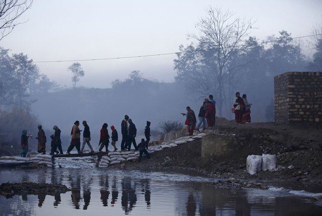 Devotees cross the Saali River during the first day of the Swasthani Brata Katha festival near Kathmandu January 5, 2015. (Photo by Navesh Chitrakar/Reuters)