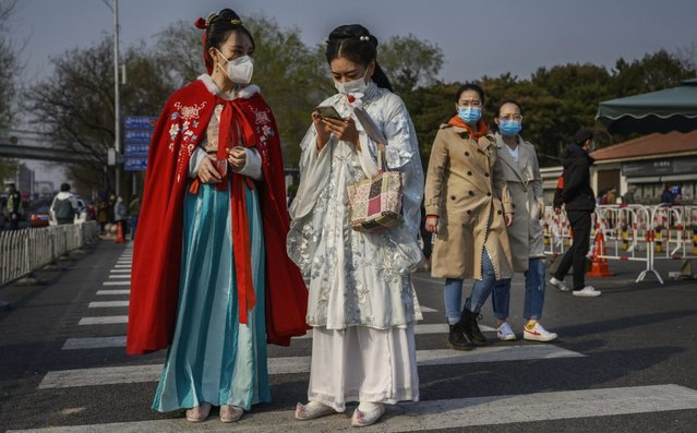 Chinese women wear protective masks as they are dressed in traditional clothing from the Qing Dynasty era outside a park on March 29, 2020 in Beijing, China. A limited section of the iconic tourist site was re-opened to the public this week allowing a smaller number of visitors to reserve tickets online in advance and to enter after passing health screening. With the pandemic hitting hard across the world, China recorded its first day with no new domestic cases of the coronavirus last week, since the government imposed sweeping measures to keep the disease from spreading. For two months, millions of people across China have been restricted in how they move from their homes, while other cities have been locked down in ways that appeared severe at the time but are now being replicated in other countries trying to contain the virus. Officials believe the worst appears to be over in China, though there are concerns of another wave of infections as the government attempts to reboot the worlds second largest economy. In Beijing, it is mandatory to wear masks outdoors, retail stores operate on reduced hours, restaurants employ social distancing among patrons, and tourist attractions at risk of drawing large crowds remain closed. Monitoring and enforcement of virus-related measures and the quarantine of anyone arriving to Beijing is carried out by neighborhood committees and a network of Communist Party volunteers who wear red arm bands. A primary concern for Chinese authorities remains the arrival of flights from Europe and elsewhere, given the exposure of passengers in regions now regarded as hotbeds for transmission. Since January, China has recorded more than 81,000 cases of COVID-19 and at least 3200 deaths, mostly in and around the city of Wuhan, in central Hubei province, where the outbreak first started. (Photo by Kevin Frayer/Getty Images)