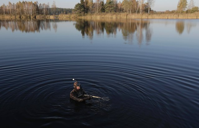 A local diver checks his equipment before diving underwater to hunt on the lake near the village of Tonovo, west of the capital Minsk, Belarus, October 18, 2016. (Photo by Sergei Grits/AP Photo)