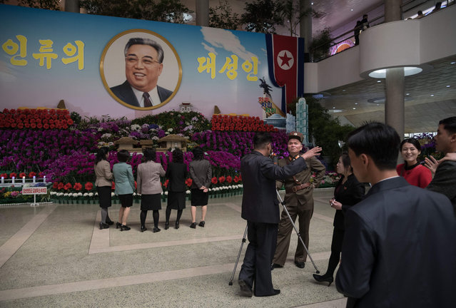 "Visitors browse the 20 th ""Kimilsungia"" festival flower show in Pyongyang on April 13, 2018. When nuclear- armed North Korea put on a flower show last year to mark the birthday of its founder Kim Il Sung, it included scale models of rockets. But taking pride of place at the national security ministry stand this year is a plant with a record 49 bloom. (Photo by Ed Jones/AFP Photo)"