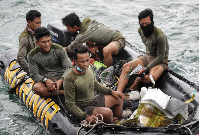 Indonesian Navy divers ride on a boat loaded with airplane parts recovered from the waters off Java Island where a Sriwijaya Air passenger jet crashed on Saturday near Jakarta, Indonesia, Sunday, January 10, 2021. Indonesian divers on Sunday located parts of the wreckage of the Boeing 737-500 at a depth of 23 meters (75 feet) in the Java Sea, a day after the aircraft with dozens of people onboard crashed shortly after takeoff from Jakarta. (Photo by Azwar Ipank/AP Photo)