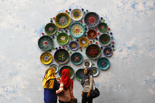 """Women look at an art installation as part of the Street Art project """"Laman Seni"""" in Shah Alam, Malaysia, 09 January 2015. Laman Seni is organized by the local council that redefines prevents unhealthy activities and make a useable space for the community at the same time enhancing the urban condition, to improve the standard of life. (Photo by Fazry Ismail/EPA)"""