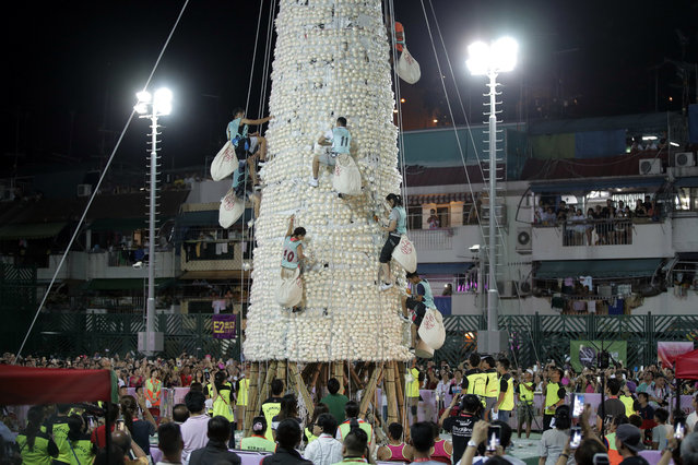 Participants climb up the bun tower during the bun snatching competition on the outlying Cheung Chau island in Hong Kong, Wednesday, May 23, 2018,  to celebrate the Bun Festival. During the Bun Festival, the Taoist God of the Sea, is worshipped and evil spirits are scared away by loud gongs and drums during the procession. The celebration includes bun scrambling, parades, opera performances, and children dressed in colorful costumes. (Photo by Kin Cheung/AP Photo)