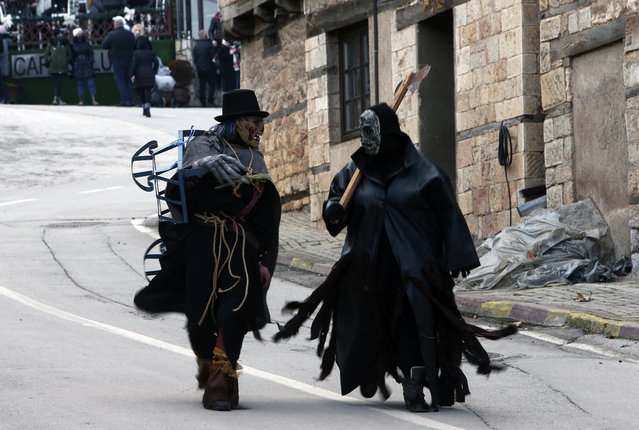 Costumed revelers walk through a street prior to the carnival parade in the village of Vevcani, in the southwestern part of North Macedonia, on Wednesday, January 13, 2021. The coronavirus pandemic has disrupted the usual carnival celebrations which have been taken place for centuries in the tiny North Macedonian town of Vevcani. A few hundred locals gathered at the small town square to celebrate the carnival, but police dispersed the gathering after a brief scuffle with a small group. No arrests or injuries were reported. (Photo by Boris Grdanoski/AP Photo)