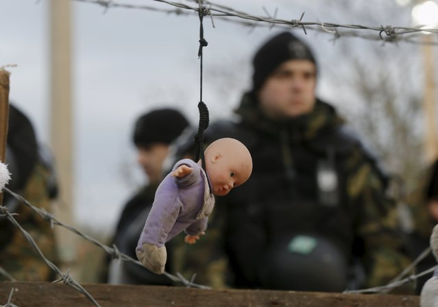 A doll, placed by stranded Iranian migrant protesters, hangs from barbed wire in front of Madedonian police at the Greek-Macedonian border near to the Greek village of Idomeni November 29, 2015. The protesters were demonstrating against what they say is the closure of the border for Iranian migrants. (Photo by Yannis Behrakis/Reuters)