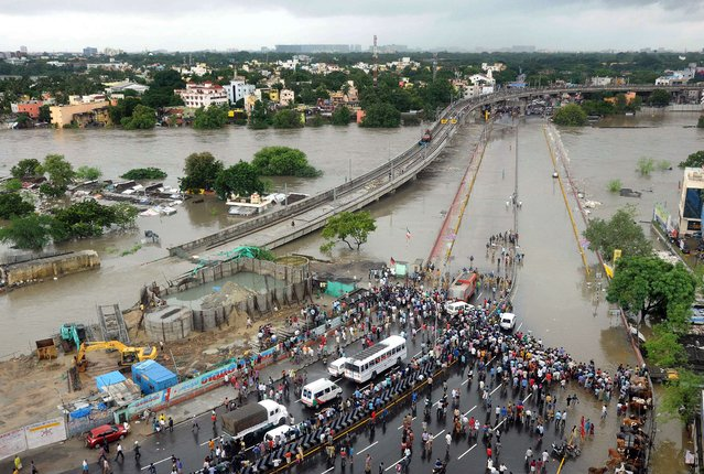 Indian bystanders and travellers gather as floodwaters lap at the end of a highway in Chennai on December 2, 2015. (Photo by AFP Photo/Stringer)