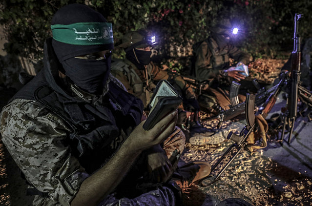 Fighters of Ezz al-Din Al-Qassam brigades, the military wing of the Hamas movement, read from the holy Quran during Laylat al-Qadr (Night of Decree), which is considered one of the holiest nights of Ramadan, near the border with Israel in the northern Gaza Strip, 11 June 2018. In Islamic belief Laylat Al-Qadr marks the night when the first verses of the Koran were revealed to the Prophet Mohammed. Muslims around the world celebrate the holy month of Ramadan by praying during the night time and abstaining from eating and drinking, smoking and sexual relations during the period between sunrise and sunset. Ramadan is the ninth month in the Islamic calendar and it is believed that the Koran's first verse was revealed during its last 10 nights. (Photo by Mohammed Saber/EPA/EFE)