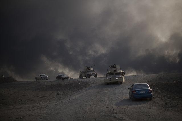 Armored vehicles move towards Hamam al-Alil from Qayara, south of Mosul, Iraq, Sunday, November 6, 2016. (Photo by Felipe Dana/AP Photo)