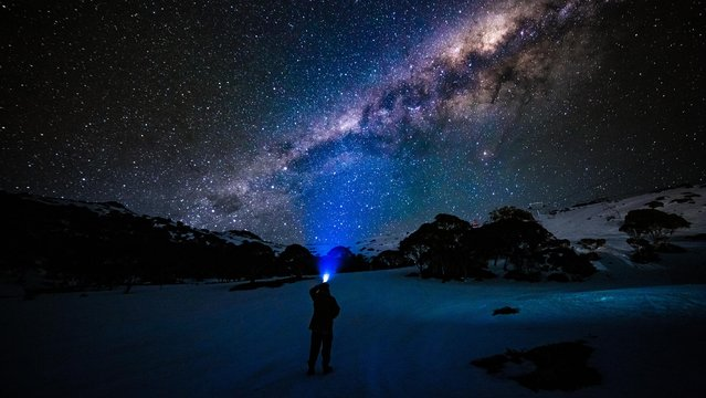 A person shines a torch into the night sky on the ski fields on September 14, 2020 in Charlotte Pass, Australia. Visitors to the Charlotte Pass ski resort have been enjoying spring snow conditions, with the ski season expected to continue until 4 October 2020. Charlotte Pass has an elevation of 1837 metres and has escaped some of the higher temperatures in lower resorts which has the snow melting earlier than others. (Photo by Bill Blair#JM/Getty Images)