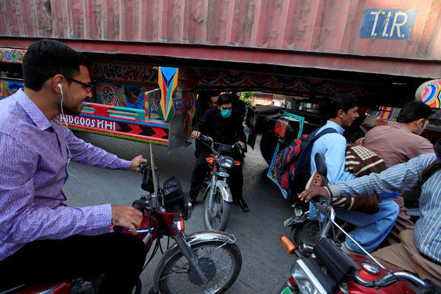 A motorcyclist slips through a gap in a barricade set up using shipping containers near the venue of a planned protest gathering organised by Awami Muslim League (AML), a political ally party of Imran Khan's Pakistan Tehreek-e-Insaf (PTI), in Rawalpindi, Pakistan, October 28, 2016. (Photo by Faisal Mahmood/Reuters)