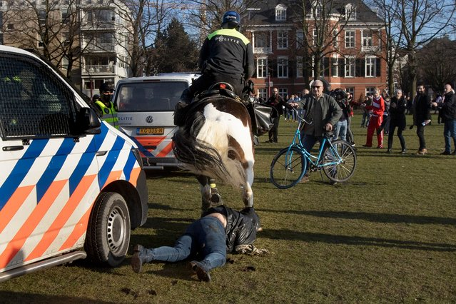 A woman gets trampled by a police horse during a demonstration of several hundreds of people protesting against the coronavirus lockdown and curfew in Amsterdam, Netherlands, Sunday, February 21, 2021. (Photo by Peter Dejong/AP Photo)