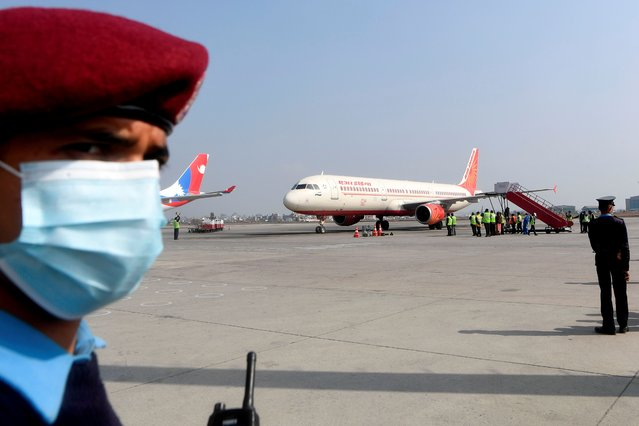 A policeman watches as an aircraft from India carrying Covishield, AstraZeneca-Oxford's Covid-19 coronavirus vaccine made by India's Serum Institute, arrives at the Tribhuvan International Airport in Kathmandu on January 21, 2021. (Photo by Prakash Mathema/AFP Photo)