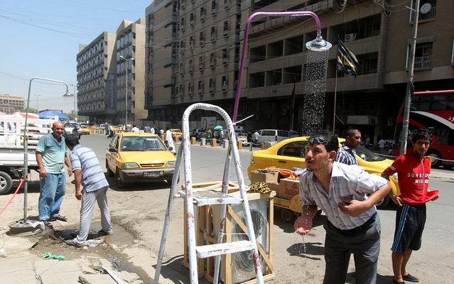 Showers are set-up along a street in the capital Baghdad as temperature soar during the Muslim fasting month of Ramadan, on July 15, 2013. Throughout the month, devout Muslims must abstain from food and drink from dawn until sunset when they break the fast with the Iftar meal. (Photo by Ahmad Al-Rubaye/AFP Photo)