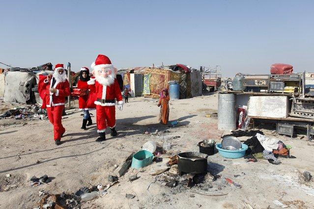 Volunteers wearing Santa Claus costumes distribute presents to the poor in Najaf, south of Baghdad, December 19, 2015. (Photo by Alaa Al-Marjani/Reuters)