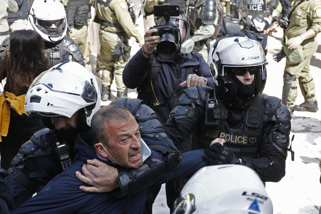 """Riot police officers scuffle with demonstrators trying to protest in solidarity with Dimitris Koufontinas, a convicted member of the guerilla group """"17 November"""", in Athens, Greece, 06 March 2021. Dimitris Koufontinas has been on a hunger strike for 58 days demanding to be transfered to Athens' Korydallos security prison from a prison in northern Greece in order to be close to his family. (Photo by Alexandros Vlachos/EPA/EFE)"""