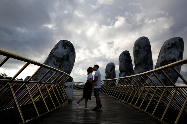 A young couple kiss near the giant hands structure on the Gold Bridge on Ba Na hill near Danang city, Vietnam on August 1, 2018. (Photo by Reuters/Kham)
