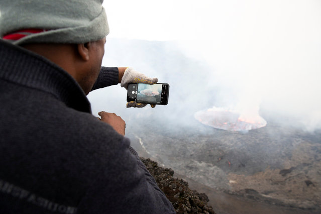 Volcano researcher Honore Ciraba takes a photograph of the lava lake on Mount Nyiragongo volcano inside the Virunga National Park, near Goma, in the eastern Democratic Republic of Congo on February 12, 2021. Analysts say the crater of Mount Nyiragongo in the eastern Democratic Republic of Congo has refilled with magma, raising the crater floor and fears of an even bigger disaster if an earthquake were to cause a fracture in the flank of the volcano. (Photo by Hereward Holland/Reuters)