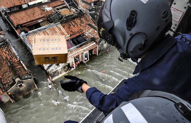 A rescue worker throws a box containing water out of a helicopter above a flooded area in Shantou, Guangdong province, China, on August 21, 2013. Flooding triggered by rainstorms have ravaged the city for the last few days, affecting 772,000 people across 11 townships, according to local media. (Photo by China Daily)