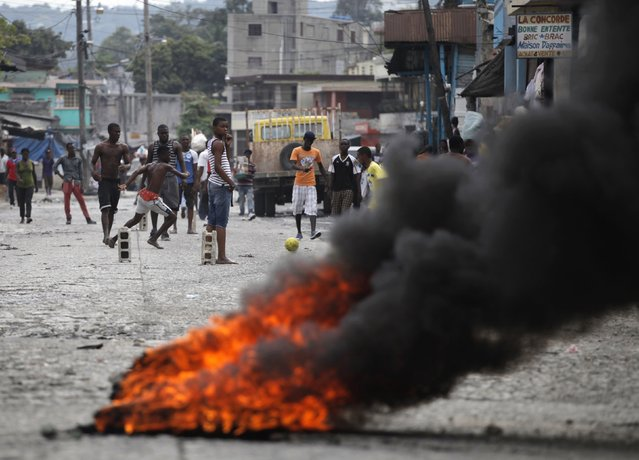 People play soccer on a street blocked by burning tyres during an anti-government protest in Port-au-Prince Feburary 9, 2015. Anti-government street protesters plan to shut down Haiti's capital for two days starting Monday as the country plunges deeper into political and economic crises even as many prepare for the annual Carnival, normally a time of peaceful revelry. (Photo by Andres Martinez Casares/Reuters)