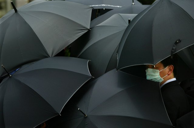 A mourner wearing a mask to ward off SARS hides under an umbrella during the  funeral of SARS doctor Tse Yuen-man in Hong Kong in this May 22, 2003 file photo. Between November 2002 and July 2003, an outbreak of SARS in southern China caused 774 deaths in multiple countries with the majority of cases in Hong Kong according to the World Health Organization (WHO). (Photo by Bobby Yip/Reuters)