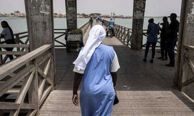 A Catholic Nun walks along a bridge towards the Island of Fadiouth, Senegal on April 3, 2021. (Photo by John Wessels/AFP Photo)