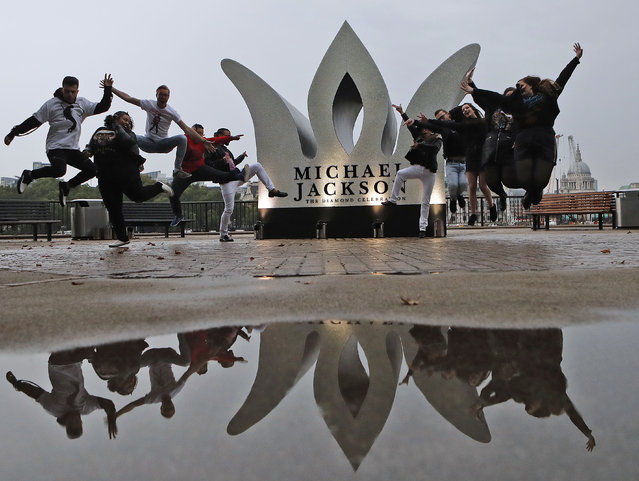 Fans of the former King of Pop Michael Jackson pose for photographers to celebrate Jacksons Diamond Birthday Celebration with the installation of a giant 13 foot jewelled crown at London's iconic Southbank in London, Wednesday, August 29, 2018. (Photo by Frank Augstein/AP Photo)