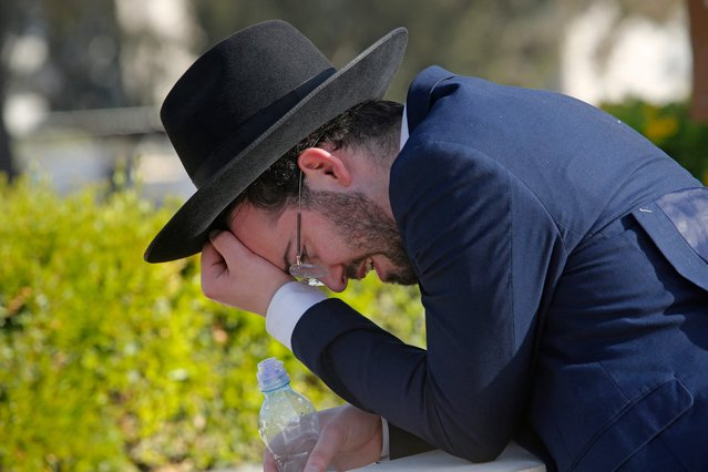 An Ultra-Orthodox Jew mourns at Segula cemetery in Petah Tikva during the funeral of a victim of Jewish pilgrim stampede, on April 30, 2021. A massive stampede at a densely packed Jewish pilgrimage site killed at least 44 people in northern Israel. The tragedy struck after pilgrims thronged to the reputed site of Rabbi Shimon Bar Yochai's tomb at Mount Meron, where mainly ultra-Orthodox Jews mark the Lag BaOmer holiday. (Photo by Gil Cohen-Magen/AFP Photo)