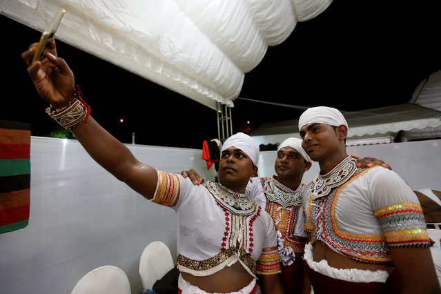 Traditional dancers take a selfie before the performances at a Gara demon ceremony in Colombo, Sri Lanka November 25, 2016. (Photo by Dinuka Liyanawatte/Reuters)