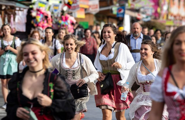 Women wearing Dirndl, a traditional Alpine folk dress, run to get a place in a tent for the opening of the 185th Oktoberfest beer festival in Munich, Germany, 22 September 2018. The Munich Beer Festival is the world's largest traditional beer festival and runs from 22 September to 07 October. (Photo by Lukas Barth-Tuttas/EPA/EFE)