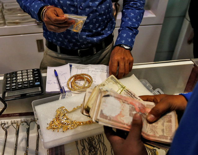 A customers pays after buying gold ornaments at a jewellery showroom during Dhanteras, a Hindu festival associated with Lakshmi, the goddess of wealth, in Mumbai, India October 28, 2016. (Photo by Danish Siddiqui/Reuters)