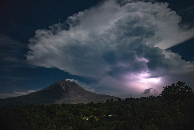 This picture taken on April 28, 2018 shows lighting and thunder over Mount Sinabung volcano in Karo. Sinabung roared back to life in 2010 for the first time in 400 years, after another period of inactivity it erupted once more in 2013, and has remained highly active since. (Photo by Lana Priatna/AFP Photo)
